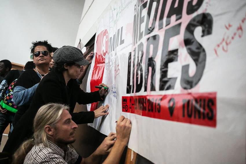 Photo : sur une grande bannière blanche du Forum mondial des médias libres, une dizaine de personnes signent leurs nom ou celui de leur média. C'est à Tunis en 2015 dans une salle aux murs blancs.